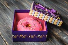 Beignet coloré dans un beau boîte-cadeau pourpre Image stock
