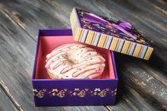 Beignet coloré dans un beau boîte-cadeau pourpre Photographie stock libre de droits