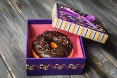 Beignet coloré dans un beau boîte-cadeau pourpre Photos libres de droits