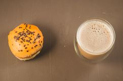 beignet dans le lustre et un cappuccino /donut en verre dans le lustre et un verre de cappuccino sur un fond brun Vue supérieure photographie stock libre de droits