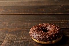 Beignet de chocolat avec le glaçage sur une table en bois brune avec l'espace pour une inscription photo stock