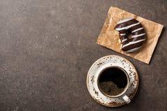 Beignet de chocolat et tasse de café sur la table image libre de droits