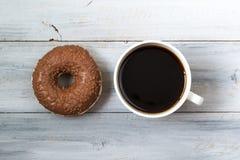 Beignet de chocolat et tasse de café noir, vue supérieure sur le fond en bois Image libre de droits