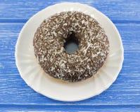 Beignet de chocolat sur un petit déjeuner en bois bleu de fond photo stock
