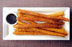 Beignet espagnol Churros nouvellement fabriqué avec du chocolat foncé s de plongement Image stock