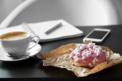 Beignet et tasse de café savoureux Photographie stock libre de droits