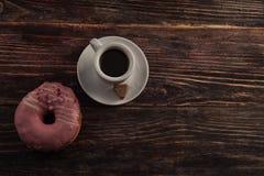 Beignet frais avec du café sur la table en bois Photographie stock libre de droits