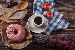 Beignet frais avec du café sur la table en bois avec la serviette, la cuillère et le c Photo stock
