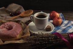 Beignet frais avec du café sur la table en bois avec la serviette, la cuillère et le c Photos libres de droits