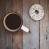 beignet frais avec la tasse de café sur la table en bois photographie stock