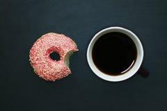 Beignet mordu dans le lustre rose et tasse de café sur le fond foncé, vue d'en haut photos libres de droits