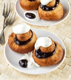 Beignets with chocolate and cream. Sweet dessert of beignets with chocolate and cream royalty free stock photo