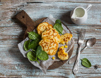 Beignets de maïs gratuits de gluten et épinards frais sur un conseil en bois images stock
