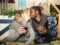 Beijando pares felizes: homem negro e mulher branca com vidro do vinho Fotos de Stock