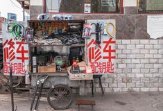 Street side bicycle repair booth, Beijing. Beijing, China - April 26, 2010: Ambulant small street-side bicycle repair booth with plenty of material on display stock photos