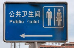 Blue Public Toilet sign along street, Beijing. Beijing, China - April 26, 2010: Closeup of blue Public Toilet sign on pole along street shows Mandarin and Royalty Free Stock Photography