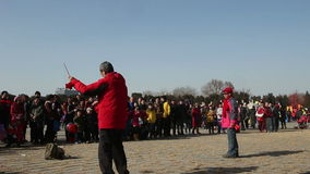 Beijing,China-Feb 2, 2014: Lots of people watch the old man and woman play diabolo together at temple fair. Beijing, China-Feb 2, 2014: Lots of people watch the