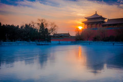 BEIJING, CHINA - 29 JANUARY, 2017: Beautiful temple building inside forbidden city, typical ancient Chinese architecture. Frozen lake in front with sunrise in Royalty Free Stock Images