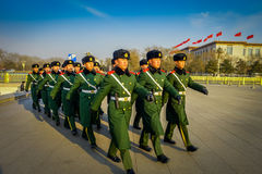 BEIJING, CHINA - 29 JANUARY, 2017: Chinese army soldiers marching on Tianmen square wearing green uniform coats and. Black hats, beautiful blue sky Royalty Free Stock Photos