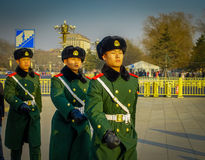 BEIJING, CHINA - 29 JANUARY, 2017: Chinese army soldiers marching on Tianmen square wearing green uniform coats and. Black hats, beautiful blue sky Stock Photos