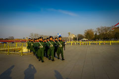 BEIJING, CHINA - 29 JANUARY, 2017: Chinese army soldiers marching on Tianmen square wearing green uniform coats and. Black hats, beautiful blue sky Royalty Free Stock Images
