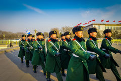 BEIJING, CHINA - 29 JANUARY, 2017: Chinese army soldiers marching on Tianmen square wearing green uniform coats and. Black hats, beautiful blue sky Stock Photo