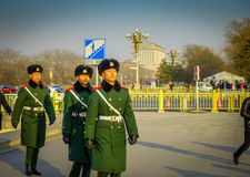 BEIJING, CHINA - 29 JANUARY, 2017: Chinese army soldiers marching on Tianmen square wearing green uniform coats and. Black hats, beautiful blue sky Stock Images