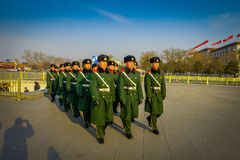 BEIJING, CHINA - 29 JANUARY, 2017: Chinese army soldiers marching on Tianmen square wearing green uniform coats and. Black hats, beautiful blue sky Royalty Free Stock Image
