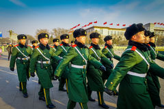 BEIJING, CHINA - 29 JANUARY, 2017: Chinese army soldiers marching on Tianmen square wearing green uniform coats and. Black hats, beautiful blue sky Stock Image