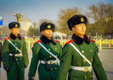 BEIJING, CHINA - 29 JANUARY, 2017: Chinese army soldiers marching on Tianmen square wearing green uniform coats and. Black hats, beautiful blue sky Royalty Free Stock Photography