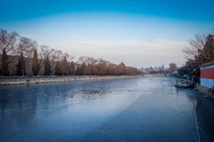 BEIJING, CHINA - 29 JANUARY, 2017: Frozen water channel inside forbidden city, trees alongside river bank, beautiful Royalty Free Stock Photography