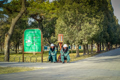 BEIJING, CHINA - 29 JANUARY, 2017: Guards wearing green uniform coats and helmets sitting resting inside temple of Royalty Free Stock Photo
