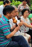 BEIJING, CHINA - JUL 17, 2011: Women and men are playing on traditional flutes in Jingshan park Royalty Free Stock Photos
