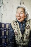 Elderly chinese grandmother relaxing in the garden stock images