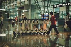 Beijing, China - June 25, 2018: Airport worker in working clothes carrying trolleys for luggage. royalty free stock images