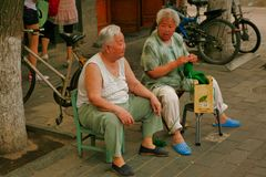 Beijing, China - June 13, 2018: Two elderly Chinese women sit in a street in Beijing and talk. stock photo