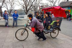 BEIJING, CHINA - MARCH 12, 2016: Tourists in a rickshaw in a hut royalty free stock photos