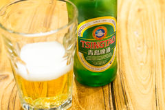 BEIJING, CHINA - MAY 22, 2016: Bottel of Tsing Tao beer beside a. Glass with sparkling beer Royalty Free Stock Photo