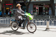 BEIJING, CHINA - MAY 12, 2013: Old man on electric motorbike Royalty Free Stock Photo