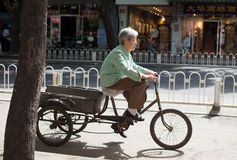 BEIJING, CHINA - MAY 12, 2013: Old woman on bicycle Stock Photography