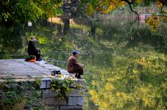 Couple sit quietly on jetty and fish at a lake outside Beijing China. Beijing, China - October 19, 2015: A man and woman sit motionless at separate ends of a Royalty Free Stock Photography