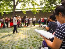 Group of middle aged and retired people singing in the park. Beijing, China - September 2017: group of middle aged and retired people singing together in the stock photo
