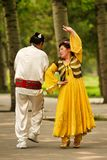 Beijing, China 07.06.2018 Woman in yellow dress and mustache man dance in the park stock image