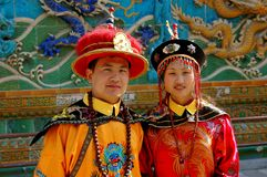Beijing, China: Young Couple in Manchu Costumes. A young married couple pose wearing traditional, colourful, ornate Manchu robes and hats at the Screen of the Royalty Free Stock Image