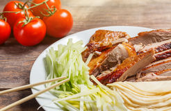 Beijing chinese Duck meat served with onions, pancakes, cucumber pieces and tomatoes on white plate with chopsticks close up. Wood Royalty Free Stock Photos