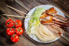 Beijing chinese Duck meat served with onions, pancakes, cucumber pieces and tomatoes on white plate with chopsticks close up. Wood Royalty Free Stock Photo