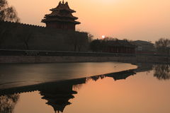 Beijing Forbidden City and reflection at sunset. The watchtower, wall and river guarding the palace, a UNESCO world heritage stock photo