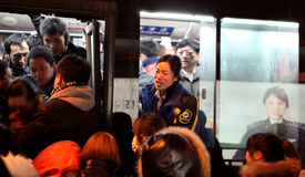 Beijing. Сhina - January 24, 2013: Girl surrounded with people on  bus station Stock Image