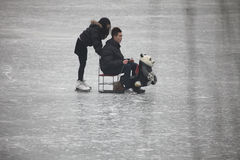 Beijing. Сhina - January 29, 2013: Unidentified couple riding on ice in , China.China's cities face serious air pollution as the development of industry Royalty Free Stock Images