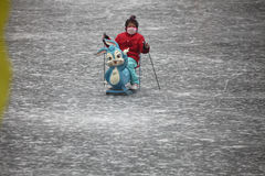 Beijing. Сhina - January 29, 2013: Unidentified female child riding on ice with pollution mask in , China.China's cities face serious air pollution as the Stock Photos